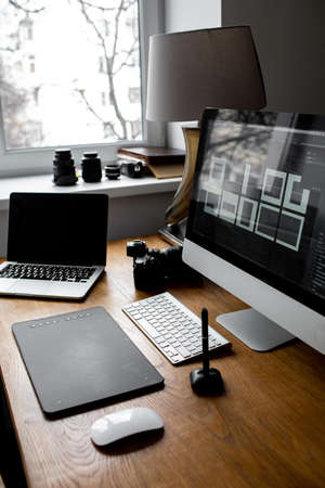 Stylish workspace with laptop on home or studio. photographers workplace.  免版税图像