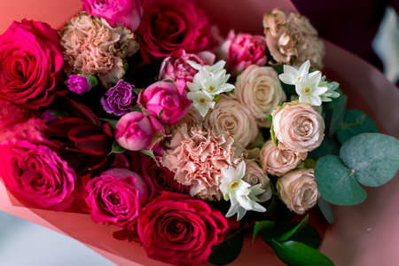Close-up flowers in hand. Florist workplace. Woman arranging a bouquet with roses, chrysanthemum, carnation and other flowers. A teacher of floristry in master classes or courses.
