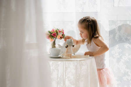 little girl in a pink skirt have breakfast, beautiful sunlight at home