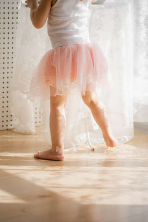 little girl in a pink skirt, beautiful sunlight at home Banco de Imagens