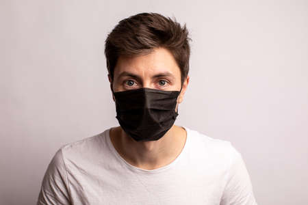 studio shot of a young man wearing a black mask, looking at camera, isolated on white background