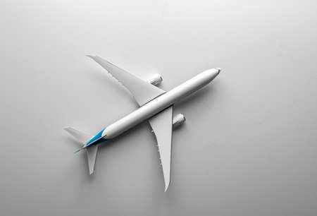 Travel concept with airplane toy over white background. Top view flat lay with copy space