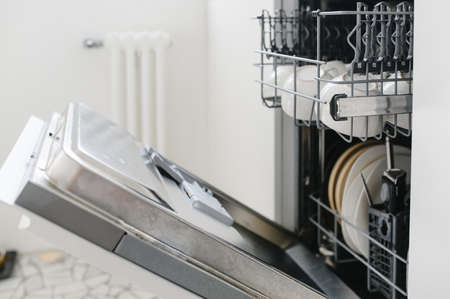 Open dishwasher with clean dishes in the white kitchen Banco de Imagens