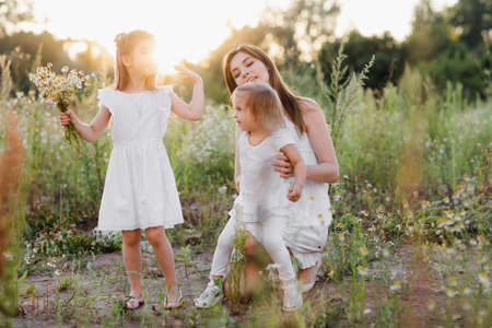 Mom and two daughters in a field at sunset. spend time together. Happy family