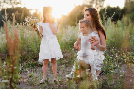 Lifestyle portrait mom and two daughter in happines at the outside in the meadow