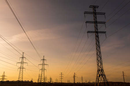high-voltage power lines at sunset. electricity distribution station