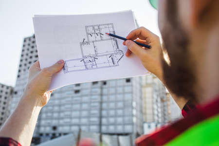 Engineering Consulting People on construction site holding blueprint in his hand. Building inspector
