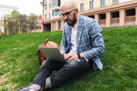 Young man using laptop outdoor. Freelance, student lifestyle, education, technology and online shopping concept