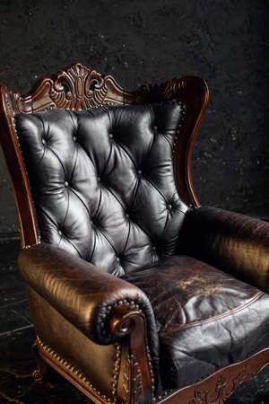 Black genuine leather classical style sofa in black room. Modern interior. Loft