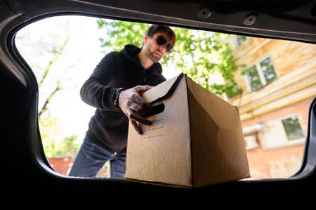 young man puts a box in the car