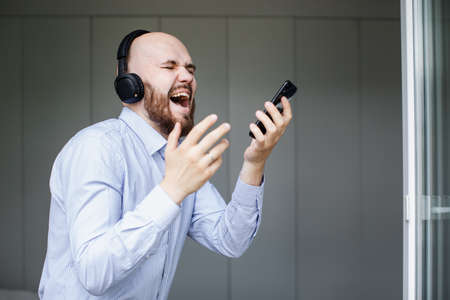 a bearded bald man sings songs and listens to music with headphones at home 写真素材