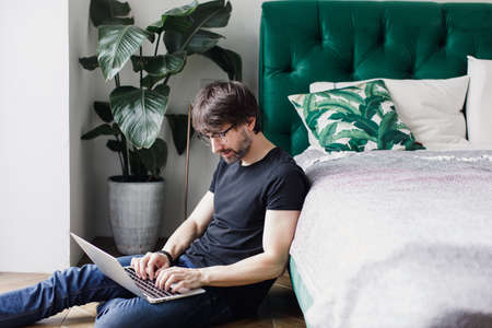 a man works on a laptop at home. Real people, people without embellishment.