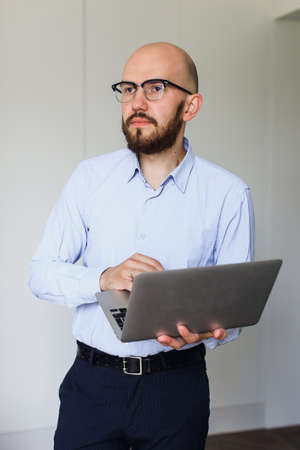 young man in glasses with a laptop stands in a bright room