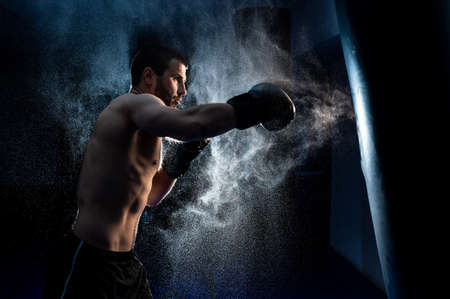 male boxer hitting a huge punching bag at a boxing studio. Man boxer training hard. Imagens