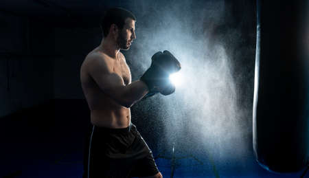 Powerful male boxer with punching bag for uppercut training