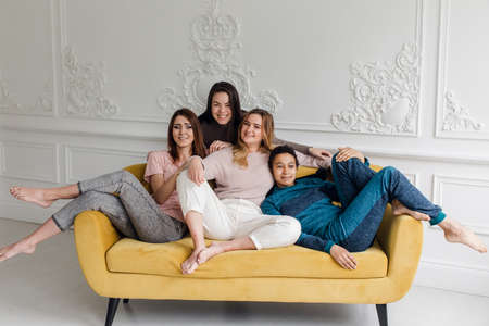 Girl friends at home watching television. Group of women with different body and ethnicity