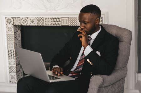 Head shot serious puzzled African American businessman looking at laptop screen. Executive managing thinking received bad news waiting hoping positive result Stockfoto