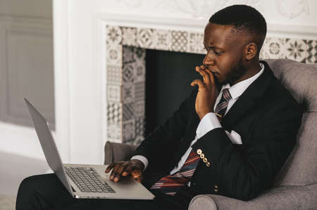Always make a total effort, even when the odds are against you. African american businessman is working, using his laptop while resting in the cafe Stock fotó