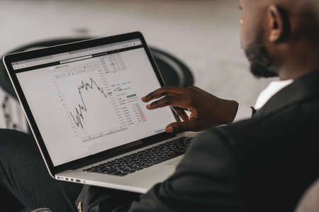 Black Businessman using laptop for analyzing data stock market, forex trading graph, stock exchange trading online, financial investment concept. close up