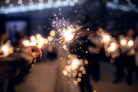 Bengal lights in male hands set fire to each other on Christmas tree lights background Banque d'images