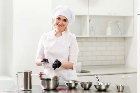 Portrait of friendly smiling female professional confectioner topping a cupcake with cream using a pastry bag