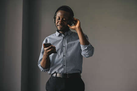Young african man listening to music with wireless earphones and dancing at home Standard-Bild