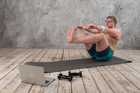 funny fat man in sports clothes doing exercises. He plays sports remotely while looking at his laptop