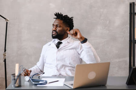 Funny bored at work african american doctor worker falling asleep at office desk, employee sleeping at workplace near laptop feel overworked concept Stock Photo