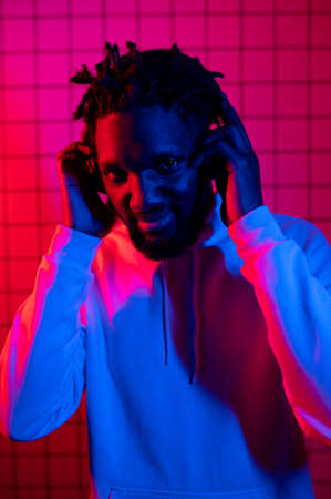 Portrait of an African American man in a hoodie on a neon background. Red-blue background.