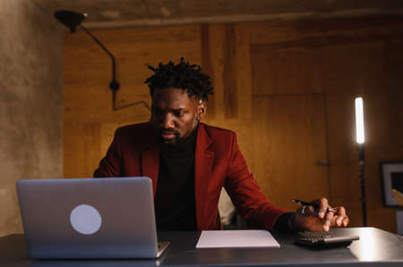 a focused black man in a suit is working on a laptop. Remote work from home Banco de Imagens