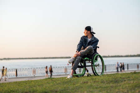 a young man in a wheelchair, walking around the city, enjoying the sunset