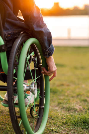 A disabled man is sitting in a wheelchair. He holds his hands on the wheel. Banco de Imagens