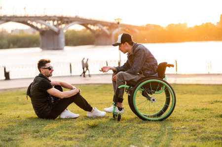a man in a wheelchair walks with his friend. Man walking with disabled friend in wheelchair at park Banco de Imagens