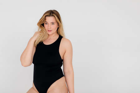 Beautiful overweight woman in black swimsuit on white background