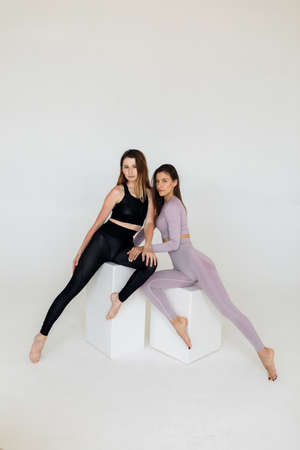 Beautiful sporty women do exercises on a white background. Fitness. Banco de Imagens