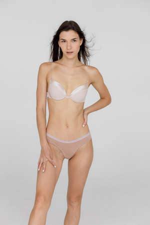 Close up shot fit woman in lingerie isolated on white background. Torso of slim attractive female with flat belly in white underwear. Copy space for text. Banco de Imagens