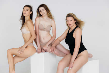 Beautiful fat girls in black lingerie on pink background. Body positive concept. Group of women with different body and ethnicity