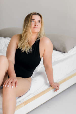 body positive. A woman in black underwear poses on a modern white interior