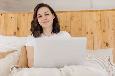 young attractive woman lying on a bed in working on a laptop. Remote work from home. E-learning