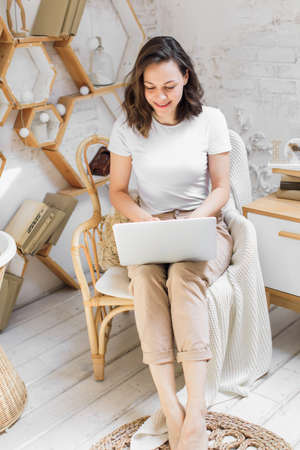 a young attractive woman in a bright modern apartment uses a laptop to communicate or study online