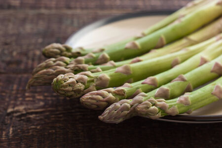 top seven: Raw asparagus steams on a white plate on the wooden table