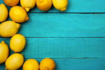 Yellow colorful lemons in the left side of the bright cyan wooden table horizontal