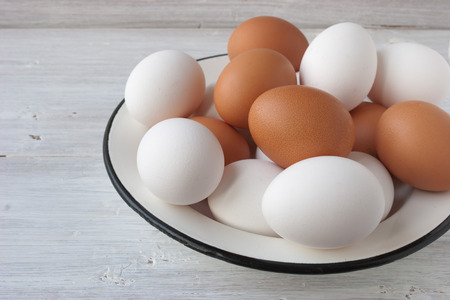 metall: Chicken eggs in a metall dish on the white boards horizontal Stock Photo