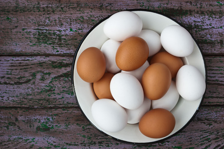 metall and glass: Chicken eggs in a glass and a metall dish on the purple aged boards