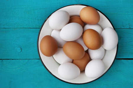 metall: Chicken eggs in a metall dish on the blue boards Stock Photo