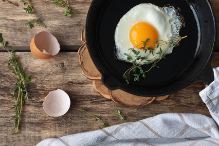 pans: Scrambled eggs in an iron pan on the rustic wooden table Stock Photo