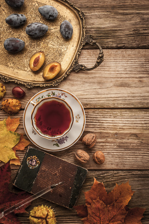 tea filter: Plums , nuts and leaves with vintage notebook and tea with film filter effect top view Stock Photo