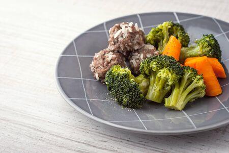 plato del buen comer: Las zanahorias y el br�coli con alb�ndigas en la placa gris horizontal
