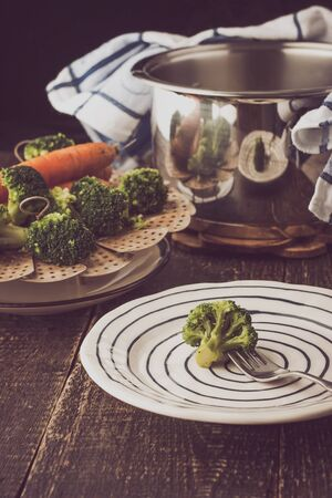 plato del buen comer: Steamed vegetables with broccoli on a fork on the wooden table Foto de archivo