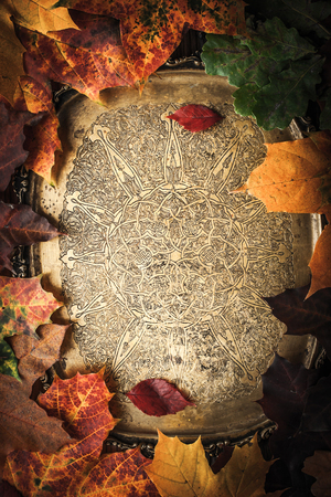 samhain: Vintage brass tray surrounded by autumn leaves